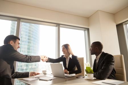 Apretón de manos de socios caucásicos femeninos y masculinos alegres sobre el escritorio de oficina, reunión multiétnica con empresario afroamericano, conclusión exitosa de acuerdo, formación de buena asociación, acuerdo Foto de archivo - 81275880