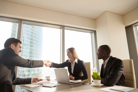 Cheerful female and male caucasian partners handshaking over office desk, multi-ethnic meeting with afro american businessman, concluding successful deal, forming good partnership, reaching agreement