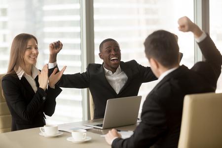 勝利を祝って、手と拍手、予期せぬ勝利、株式取引の成功、印象的な成果、大きな幸運を上げる正式な摩耗で幸せな興奮している多民族のビジネス