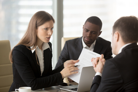Angry dissatisfied businesswoman holding contract arguing with contractor, pointing at terms failed to perform, demanding termination, loss compensation, defrauded cheated investor protecting rights