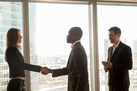 立っている近代的なオフィスに大きなウィンドウで多文化共生パートナー開始会議、ビジネスマンやビジネスウーマンのハンド シェーク知り合い、