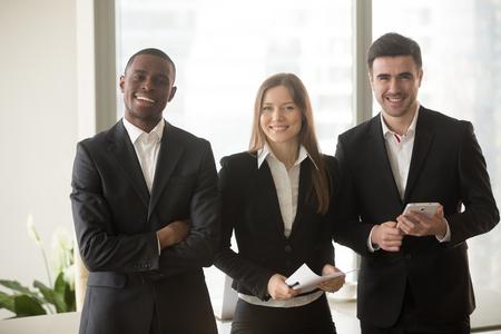 Vrolijke onderneemster in formele slijtage die zich tussen twee zekere zakenlieden bevindt die voor camera, multi-etnisch teamportret, gemotiveerde professionele adviseurs, raad van beheer, bedrijfsgroep stellen