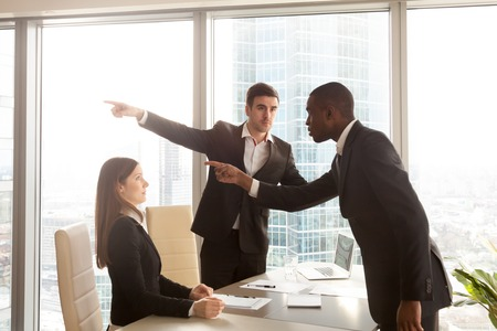 Rude black businessman behaves insultingly impolitely at meeting, pointing at shocked white woman, getting fired for inappropriate behavior, bad manners, sexism and gender discrimination at work