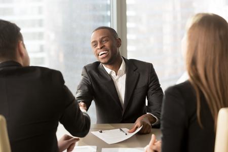Excited souriant homme d'affaires noir partenaire de la rencontre, un candidat africain réussi à être embauché, a obtenu un emploi, des hommes d'affaires multiraciaux satisfaits, serrant la main après avoir signé un document