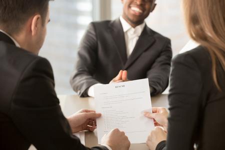 Werkgevers of recruiters beoordelen cv van zwarte zelfverzekerde sollicitant lachend op achtergrond tijdens sollicitatiegesprek, goede CV sjabloon schrijven tips, huur me, beginnen met bouwen carrière, close-up