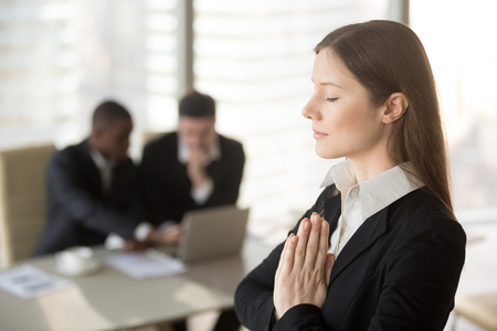 Young beautiful businesswoman enjoys meditating standing in office with eyes closed, put hands together as in prayer, reduce stress, relief to keep calm, positive thinking, appeasement, autosuggestion