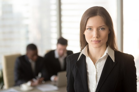 Portrait of serious attractive businesslady in office interior with male colleagues at the background, looking at camera, ambitious motivated career woman, successful female boss running own business Stock Photo