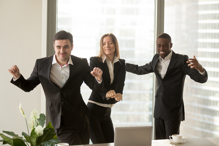 Excited african and caucasian employees dancing in office, staff party, positive multi-ethnic team satisfied with result, won profitable contract, group of winners celebrate victory or great success Stock fotó