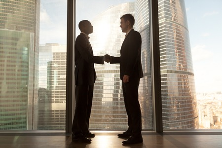 Two smiling young black and white businessmen handshaking standing near big window with city buildings outside, confident caucasian and afro american partners form good relations, reach agreement