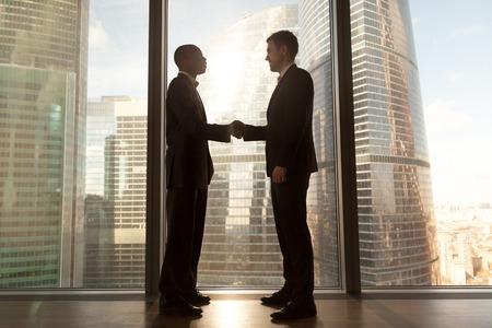Twee glimlachend jong zwart-wit zakenliedenhandenschudden die zich dichtbij groot venster met stadsgebouwen buiten bevinden, zekere Kaukasische en afro Amerikaanse partners vormen goede relaties, bereik overeenkomst