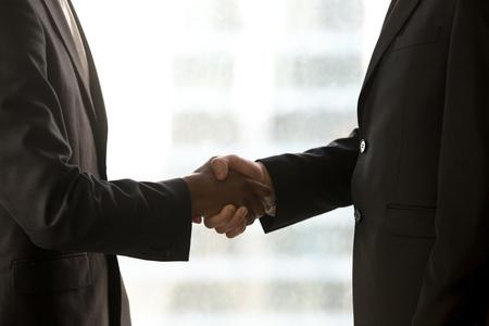 흑인과 백인 손을 흔들면서, 기업인 formalwear 핸드 셰이 킹, 국제 파트너십을 형성 거래 닫는 백인 및 미국 미국 파트너의 측면보기를 닫습니다, 멀티 민 스톡 콘텐츠