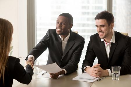 두 명의 밝은 흑백 채용 담당자가 취업 면접을 위해 여성 지원자를 환영합니다. 아프리카 및 백인 HR 관리자는 빈 자리, 핸드 쉐이킹 및 좋은 첫인상 후 스톡 콘텐츠
