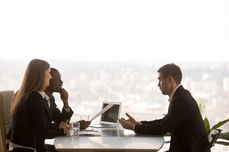 Amable gerentes de hora atento entrevistando solicitante de vacante, socios multiétnicos discutiendo idea de proyecto nuevo sentado en el escritorio de oficina con paisaje exterior, ventana grande en el fondo, vista lateral Foto de archivo