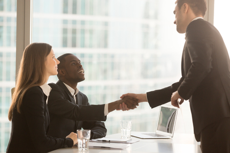 Friendly black and white recruiters sitting at office desk shaking hands with applicant just arrived for interview, diverse hr managers greeting candidate, nice to meet you and good first impression 스톡 콘텐츠