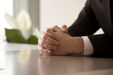 clench: Close up of male clasped hands clenched together on table, businessman preparing for job interview, concentrating before important negotiations, thinking or making decision, business concept