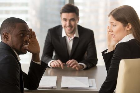 Gemischtrassige, verwirrte Arbeitgeber diskutieren verdeckt über Bewerber, verstecken das Gesicht mit den Händen, sehen verwirrt aus, flüstern heimlich während des gescheiterten Interviews, machen einen schlechten, negativen ersten Eindruck und treffen eine Entscheidung Standard-Bild