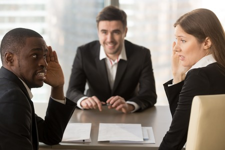 Multiracial confused employers covertly discuss job applicant, hide face with hands, look puzzled bewildered, secretly whisper during failed interview, bad negative first impression, make decision