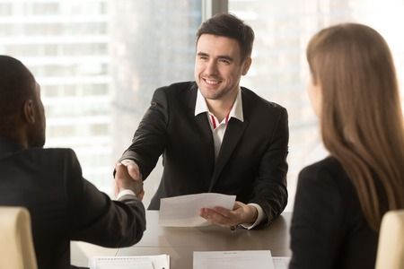 Happy applicant greeting employers at job interview, cheerful satisfied partners shaking hands, making deal agreement with friendly handshake at meeting, successful effective negotiations, get a job Stockfoto