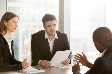 Black businessman trying to convince white doubtful partners to sign document, negotiations about contract, discussing deal, afro american job applicant persuades employers to hire, tell arguments