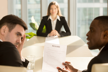 accomplishment: Funny multiethnic employers impressed by female applicant skills at job interview, black and white recruiters considering candidate shocked by great career achievements or bad poor cv, focus on resume