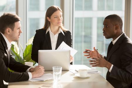Multi-etnisch commercieel team bespreken project of idee zitten aan een bureau, partners werken samen, analyseren van financieel rapport, het vinden van effectieve zakelijke oplossingen tijdens zakelijke bijeenkomst