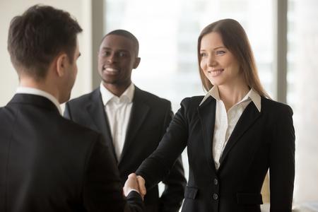 Mooie lachende zakenvrouw en zakenman handshaking staan in kantoor, leuk om je te ontmoeten, eerste indruk, wordt bevorderd beloond voor goed werk, werknemer van de maand, carriere ontwikkeling