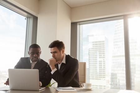 Zwei ernst schwarze und weiße Geschäftsleute diskutieren Projekt sitzen am Schreibtisch, mit PC Laptop, Blick auf Bildschirm, machen Präsentation, erstellen Business-Plan, erfüllen Aufgabe, Investition zu prüfen Standard-Bild - 80170946