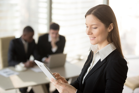 Young attractive businesswoman holding tablet, looking at screen, standing in office with colleagues at background, organizing scheduling meeting, using business app for managing time and daily tasks