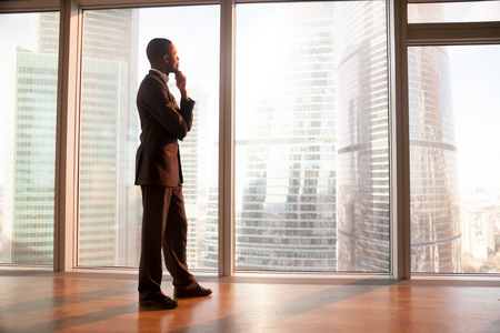 Young afro american contemplative businessman stands in office with hand on chin, looks through big window at the city, african entrepreneur enjoys sunset, rests after work, gets business inspiration Standard-Bild