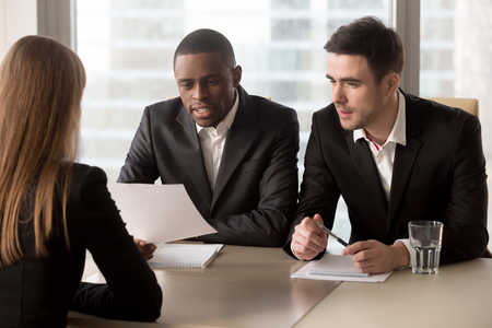 Multiracial black and white recruiters, executive hr management group interviewing female job applicant, headhunters studying cv resume of candidate, asking questions, partners discussing contract