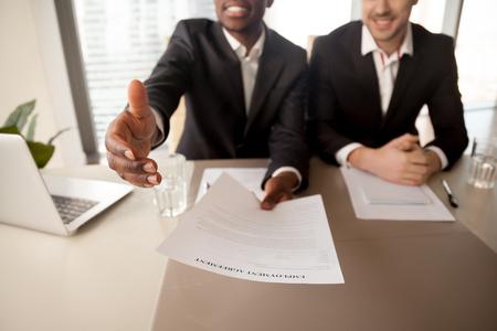 Close-up do empresário negro, oferecendo emprego, alcançando contrato de trabalho para candidato bem-sucedido, contrato de trabalho do trabalho, estendendo a mão para aperto de mão, contratação de novo funcionário, conseguir emprego Foto de archivo - 80132526
