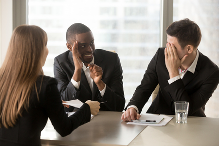 Multiracial businessmen hiding face with hands, sneaking look at each other while businesswoman presenting document, recruiters covertly discussing candidate, secretly whispering during interview Standard-Bild
