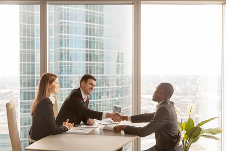 Friendly caucasian employers and confident african-american applicant handshaking during job interview sitting at office desk with big large window urban buildings cityscape at background, side view Stock Photo - 80170993
