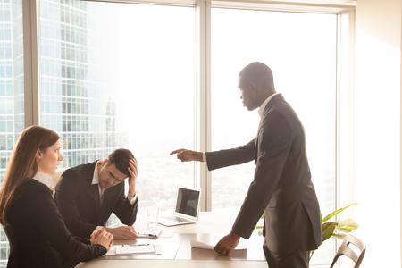 Enojado mal jefe afroamericano gritando a los empleados caucásicos, recibiendo amonestaciones con expresiones culpables y conmocionado, mostrando autoridad, señalando a un trabajador masculino cometió un error, regañando por el fracaso