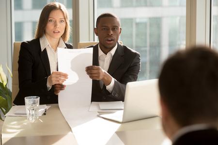 긴 면직 용지를 들고있는 Multiracial 모집 원은 취업 인터뷰에서 후보자를 놀라 울 정도로보고, 훌륭한 경력 업적, 인상적인 업적으로 상세한 이력서를