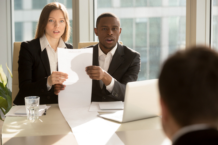 Multiracial recruiters holding long sheet of paper, looking surprisingly at candidate during job interview, prepared detailed resume with great career achievements, impressive work accomplishments Stock Photo