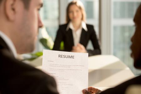 여성 취업 지원자가 배경에서 결과를 기다리는 동안 공석을 채우기 위해 고용 결정을 내린 다국적 고용주, 인터뷰에서 이력서를 들고있는 채용자를 모