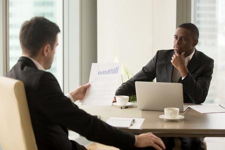 多様なパートナー情報データの分析、抜群のチームワークの結果を示す上昇グラフの財務レポートを読んで議論するスーツで企業の会議に 2 人の多 写真素材