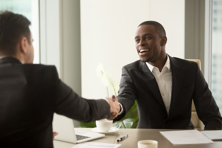 Two multicultural businessmen handshaking over desk, attractive african entrepreneur shaking hand of caucasian client, start finish negotiations, establishing multi-ethnic partnership, making deal