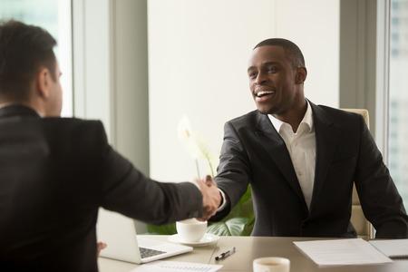 Twee multiculturele zakenlieden handshaking over bureau, aantrekkelijke Afrikaanse ondernemer schuddende hand van Kaukasische cliënt, beginnen onderhandelingen, vestigen multi-etnisch vennootschap, maken overeenkomst