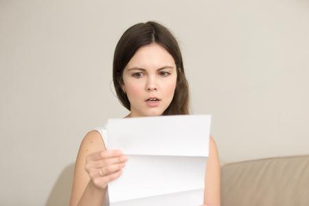 Mujer joven sorprendida leyendo carta con malas noticias. Señora atractiva preocupada mirando el documento con aviso escrito inesperado, conmocionado con facturas, formulario de impuestos o pago incorrecto. Mensaje sobre la deuda del préstamo