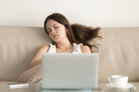 Young attractive woman falling asleep on sofa at home in front of laptop. Teenager girl resting after long hours surfing Internet. Female student takes break after finishing computer work, exam study Stock Photo