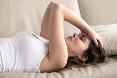 Woman lying on sofa having headache. Stressed girl suffering of fatigue, migraine, trying to cope with nervous tension, worries because of problems, unwanted pregnancy, negative thoughts and emotions