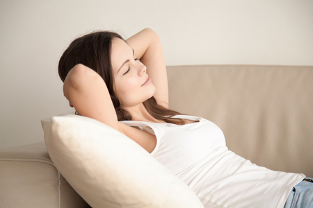 Yong attractive woman in casual clothing lying on comfort sofa. Calm beautiful lady resting with closed eyes and hands behind head on coach at home, relaxing after hard day, enjoying moment of peace