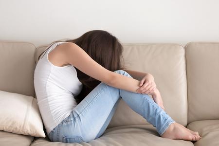 우울 된 젊은여자가 손에 무릎을 껴 안은 소파에 앉아. 스트레스를 받고 화가 난 사춘기 소녀는 감정적 인 공허함, 외로움, 관계 때문에 걱정합니다. 십 스톡 콘텐츠