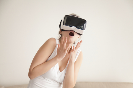 Young woman feels scared watching horror movie in VR glasses. Lady surprised with effect of presence in realistic digital simulation. Bright emotional reaction, using VR headset for the first time Stock Photo