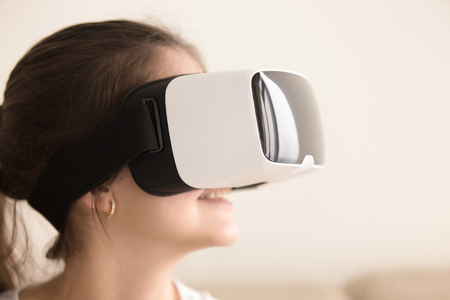 Close up portrait of young woman wearing virtual reality glasses looking on digital simulation in cyberspace. Lady entertains with 3d glasses. First experience with VR technology concept
