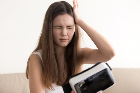 Teenage girl feels dizziness or headache after using virtual reality glasses. Woman suffers from eyes discomfort when took off VR headset. Negative side effect of being in virtual reality. VR sickness Foto de archivo