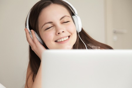 Beautiful woman in headphones takes pleasure when listens music on laptop. Happy smiling teen girl enjoying favorite tracks, exited with popular songs in Internet. Buying digital music online concept Stock Photo