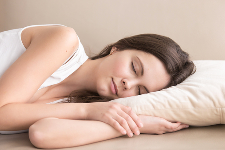Cute young woman sleeping on side on soft pillow on sofa, lying relaxed with closed eyes. Tired beautiful lady resting at home, enjoying pleasant leisure. Daytime drowsiness and nap concept. Close up Stock Photo